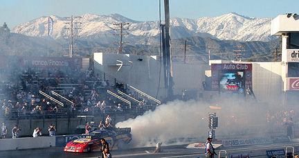 Capps' Funny Car burnout against snow capped mountains.