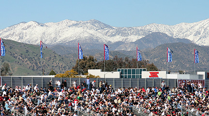 Grandstands against snow capped mountains.